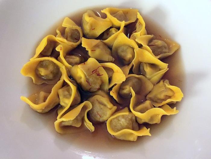 Il piatto più audace: Raviolini di cipolla caramellata in brodo di bucce di patata bruciate e infusione di porcini secchi